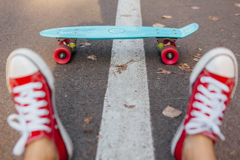 Schließen Sie oben von den Füßen und vom blauen Pennyrochenbrett mit rosa Rädern lizenzfreies stockbild