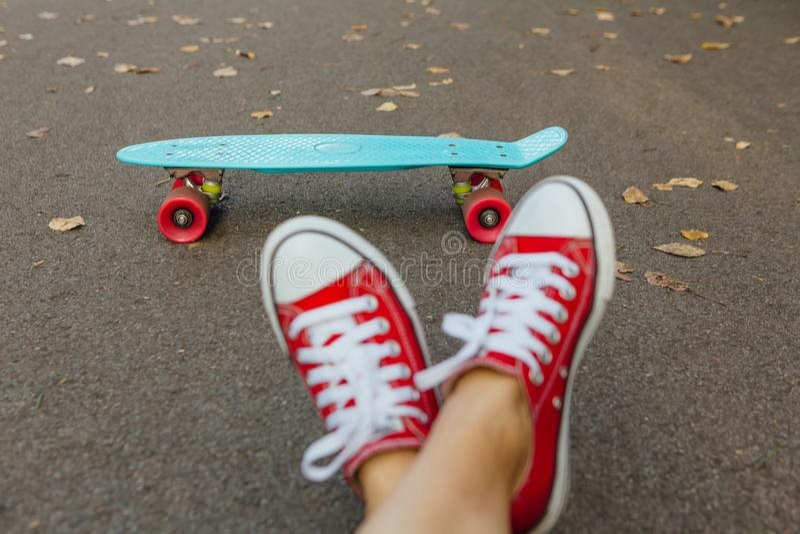 Schließen Sie oben von den Füßen und vom blauen Pennyrochenbrett mit rosa Rädern lizenzfreies stockfoto