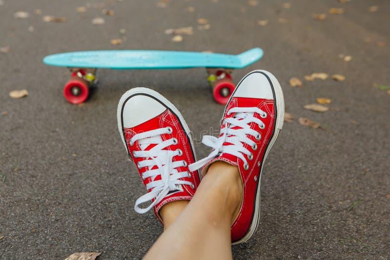 Schließen Sie oben von den Füßen und vom blauen Pennyrochenbrett mit rosa Rädern lizenzfreie stockfotos