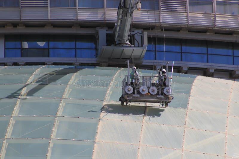 Schließen Sie oben von den Fensterputzern in einem Korb, der einen modernen Wolkenkratzer säubert lizenzfreies stockfoto