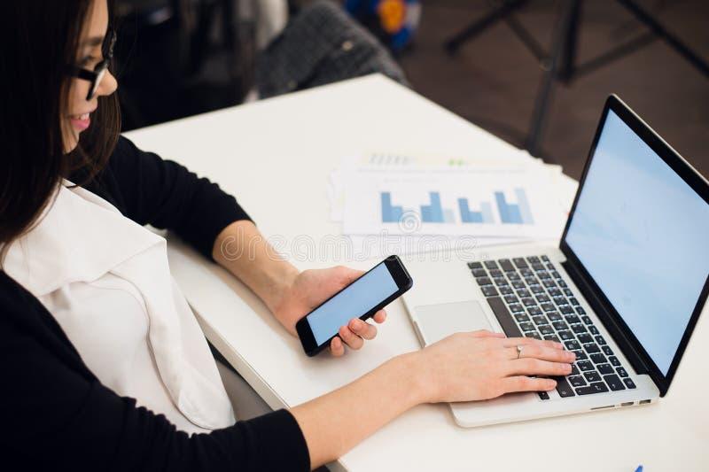 Schließen Sie oben von den Frauenhänden unter Verwendung des Handys und der Laptop-Computers mit leerem Kopienraumschirm für Ihre stockfoto