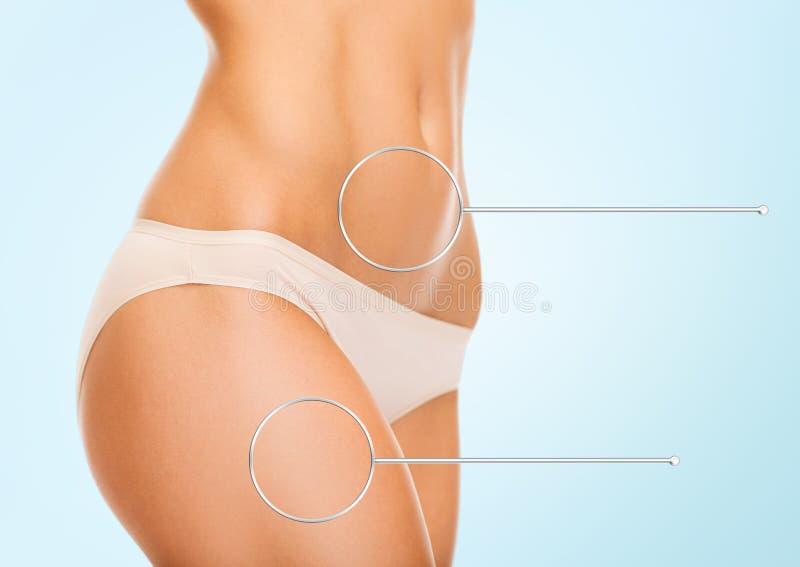 Schließen Sie oben von den Frauenhüften und -Torso mit Vergrößerungsglas lizenzfreies stockfoto