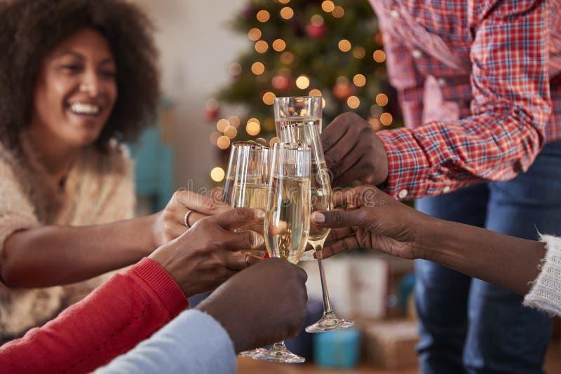 Schließen Sie oben von den Freunden, die zu Hause einen Toast mit Champagne As They Celebrate Christmas zusammen machen stockbilder