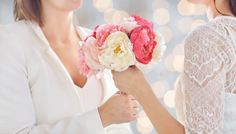 Schließen Sie oben von den glücklichen lesbischen Paaren mit Blumen stockfotografie