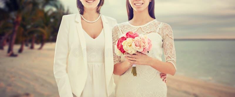 Schließen Sie oben von den glücklichen lesbischen Paaren mit Blumen lizenzfreies stockfoto