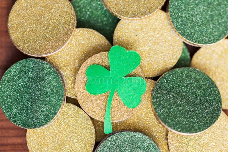 Schließen Sie oben von den goldenen Münzen und vom grünen Shamrockblatt lizenzfreie stockfotos