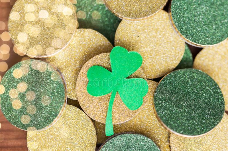 Schließen Sie oben von den goldenen Münzen und vom grünen Shamrockblatt lizenzfreies stockbild
