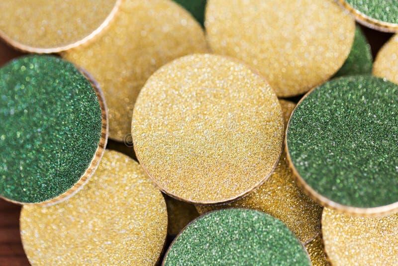 Schließen Sie oben von den goldenen und grünen Münzen lizenzfreie stockbilder