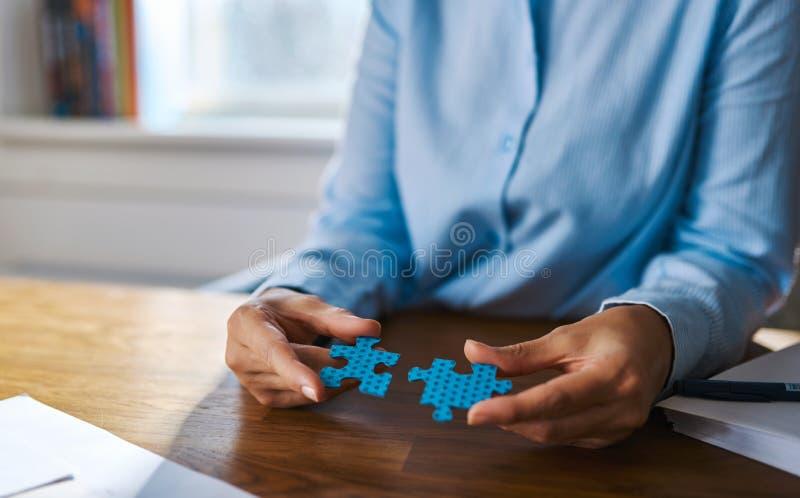 Schließen Sie oben von den Händen, die zwei Puzzlespielstücke zusammenbauen lizenzfreies stockfoto