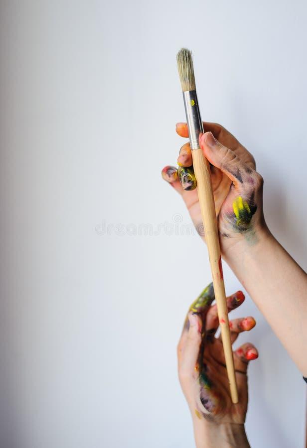 Schließen Sie oben von den Händen eines Künstlers/des Malers, die Pinsel halten stockbild