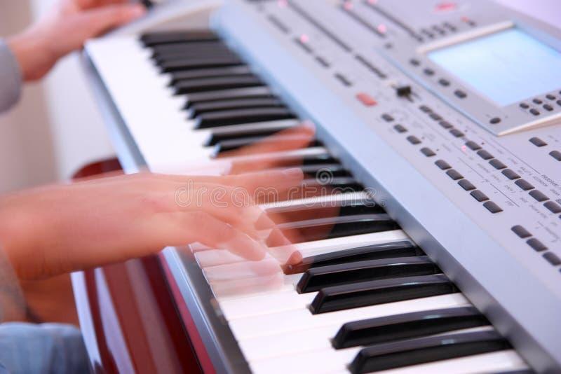 Schließen Sie oben von den Händen eines Mannes, der elektronische Tastatur oder PU spielt stockfoto