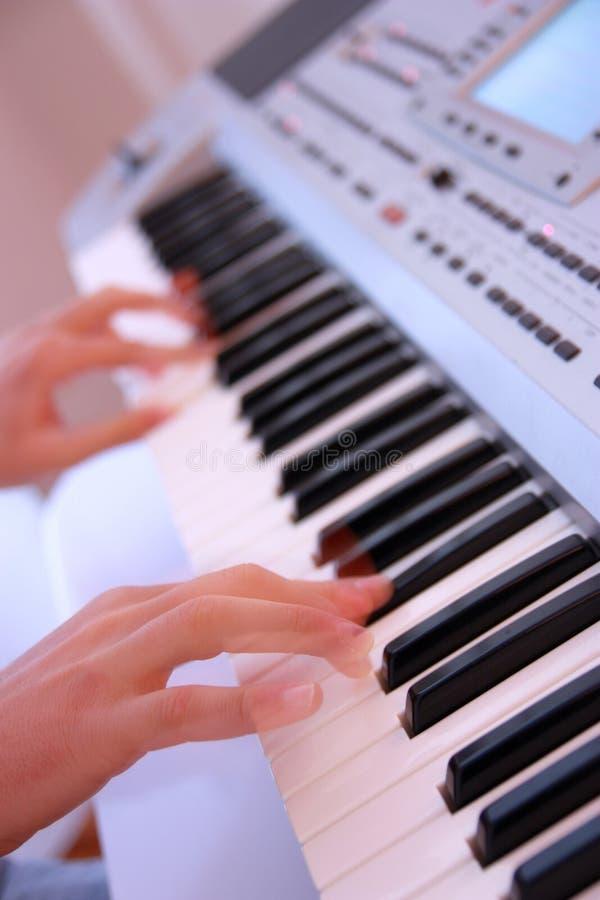 Schließen Sie oben von den Händen eines Mannes, der elektronische Tastatur oder PU spielt stockfotos