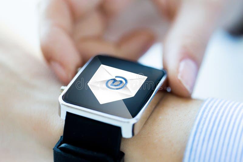 Schließen Sie oben von den Händen mit E-Mail-Ikone auf smartwatch stockfotos