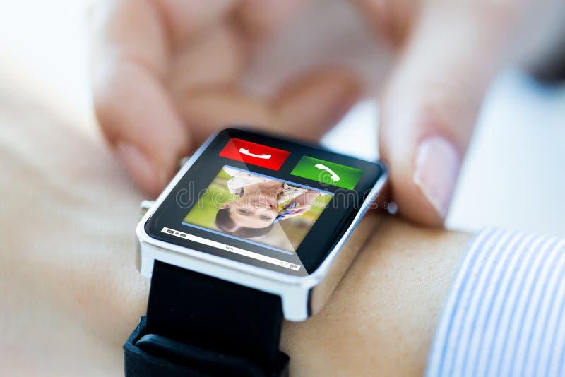 Schließen Sie oben von den Händen mit eingehendem Anruf auf smartwatch lizenzfreie stockfotografie