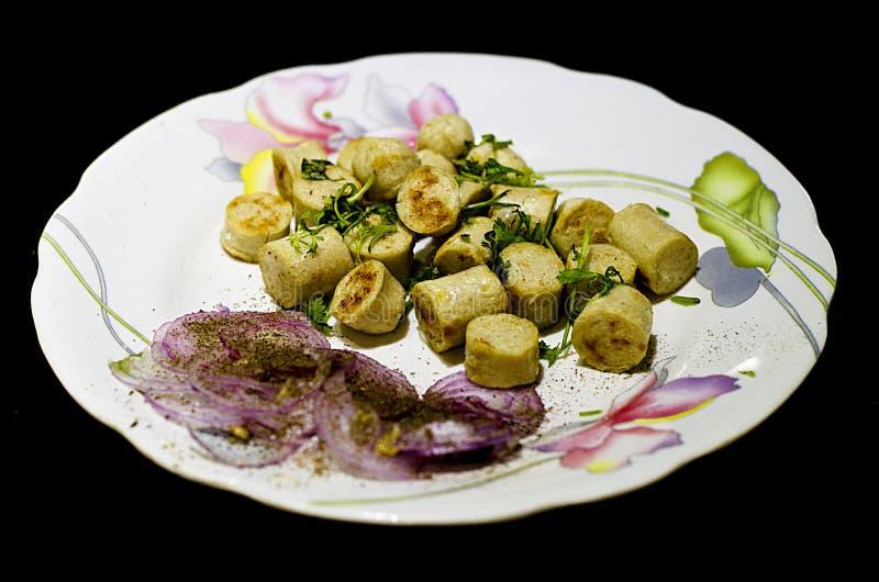 Schließen Sie oben von den Hühnerwürsten, die mit Zwiebelsalat in einer Servierplatte gedient werden lizenzfreies stockbild
