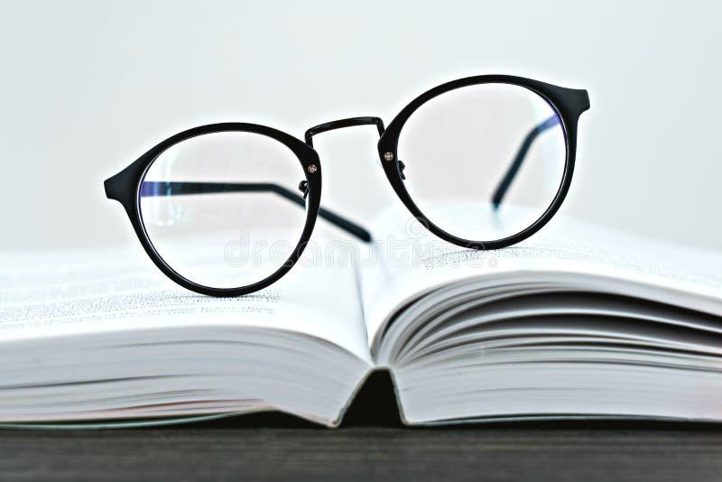 Schließen Sie oben von den Hippie-Gläsern für das Ablesen auf einem offenen Buch stockfotos