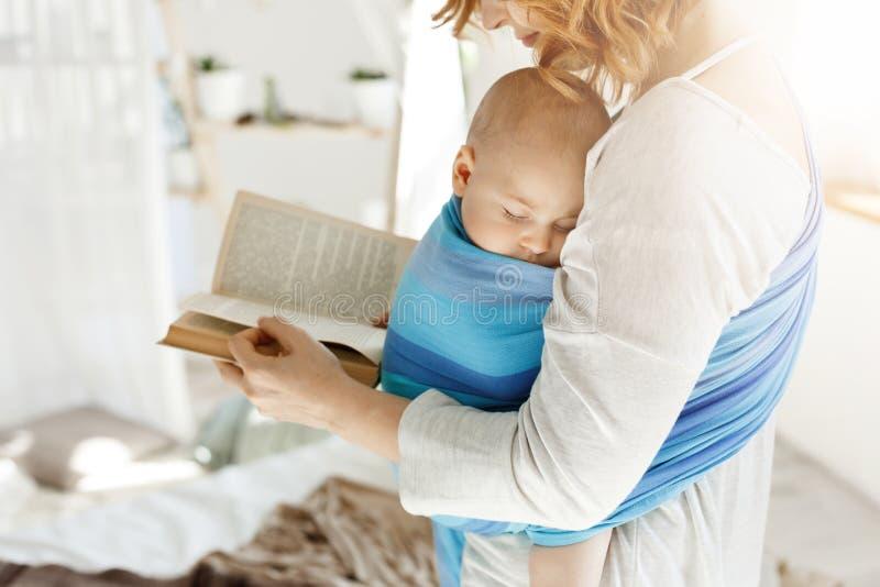 Schließen Sie oben von den jungen Mutterlesemärchen für ihren neugeborenen kleinen Sohn im bequemen hellen Schlafzimmer Baby schl lizenzfreie stockfotos