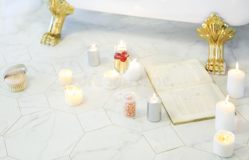 Schließen Sie oben von den Kerzen, Buch, Glas Champagner durch das Bad stockfotos