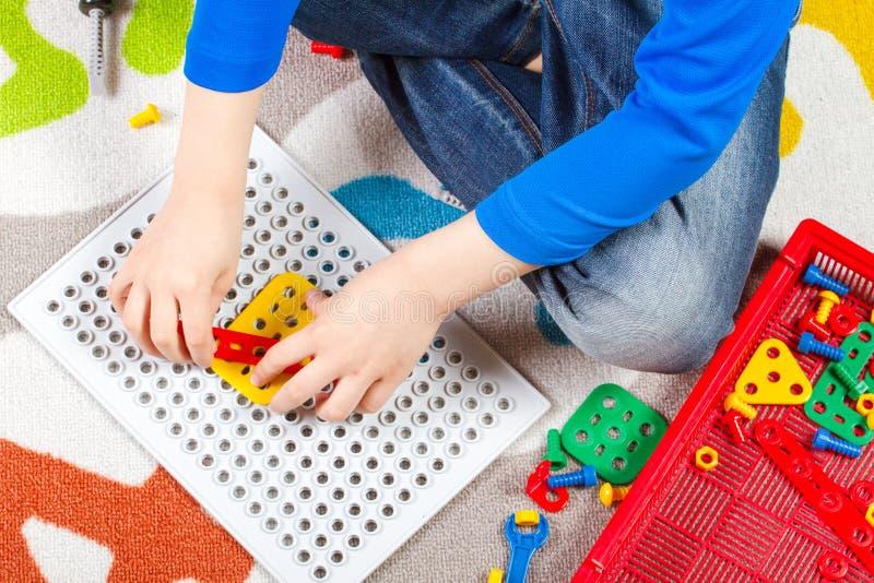 Schließen Sie oben von den Kinderhänden, die mit Spielwarentool-kit spielen Beschneidungspfad eingeschlossen stockfotografie