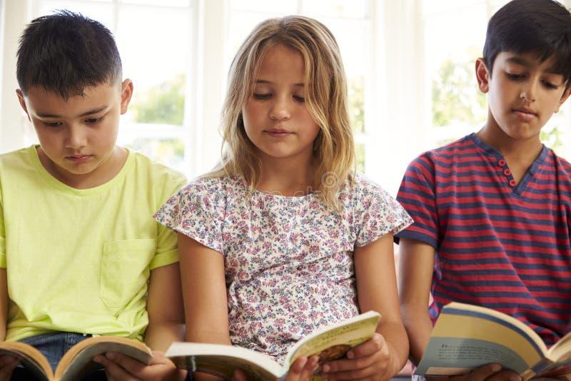 Schließen Sie oben von den Kindern, die auf Fensterplatz lesen stockfoto