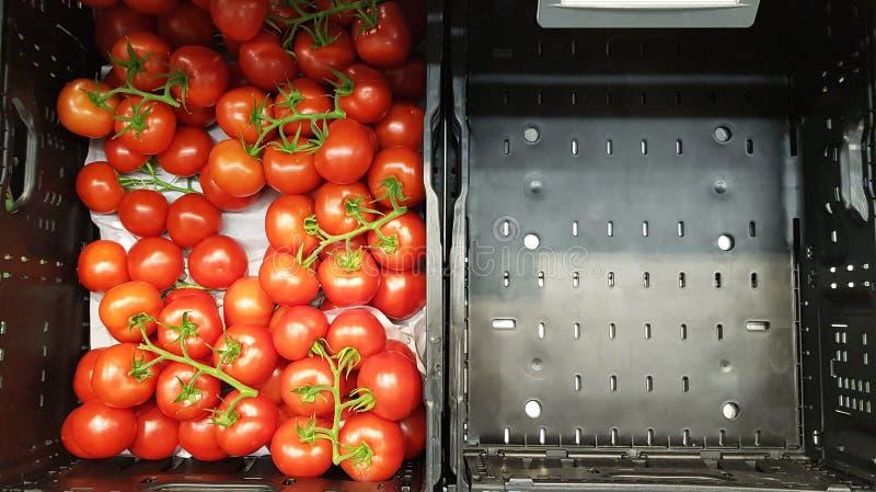Schließen Sie oben von den Kirschtomaten im vollen schwarzen Plastikkorb und im leeren Korb auf dem Supermarkt lizenzfreie stockfotos