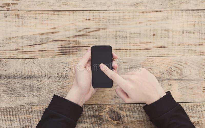 Schließen Sie oben von den männlichen Händen, die Smartphone halten und Finger zeigen, um auf hölzernen Planken des Schirmes bei  lizenzfreie stockbilder