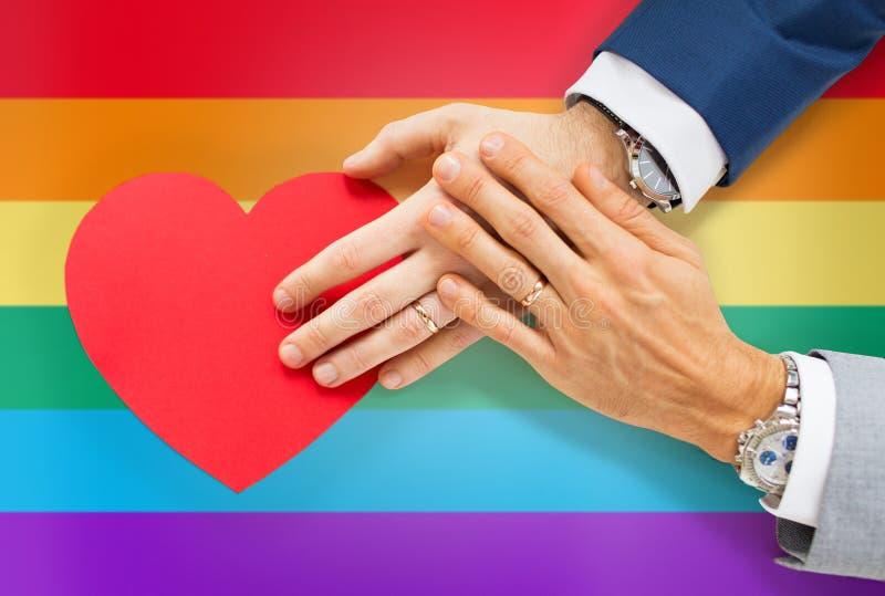 Schließen Sie oben von den männlichen homosexuellen Paarhänden mit rotem Herzen lizenzfreie stockbilder