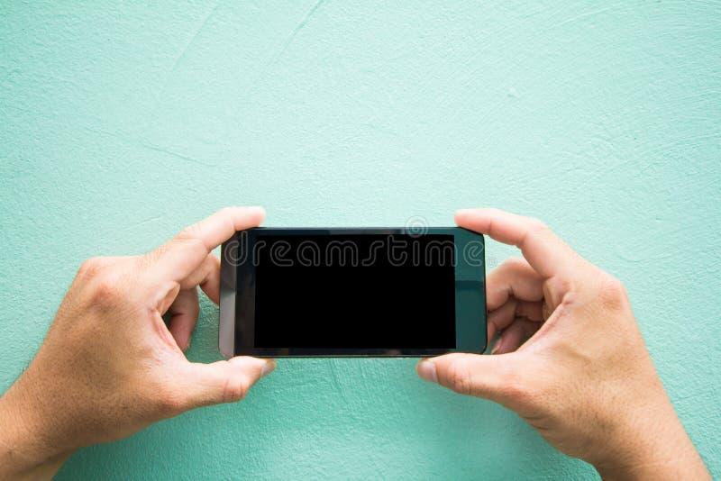 Schließen Sie oben von den Mannhänden, die das Berühren des Spielspielhandys mit leerem Kopienraum für Ihre Textnachricht auf grü stockfotos
