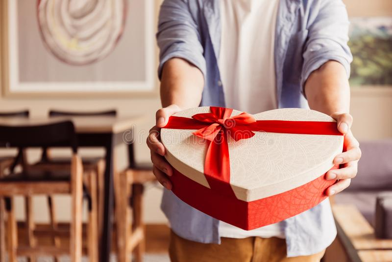 Schließen Sie oben von den Mannhänden, die ein anwesendes Geschenk in Richtung zur Kamera geben - Feiertagsthema - im warmen Sonn