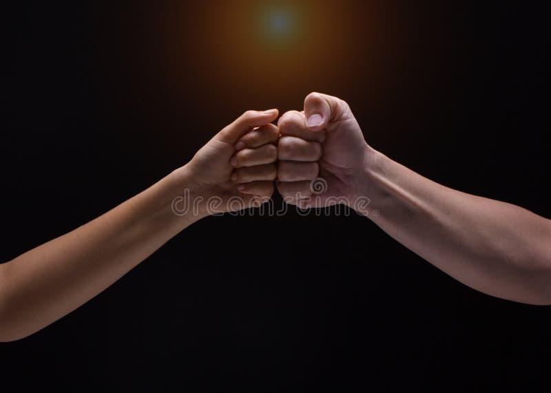 Schließen Sie oben von den menschlichen Händen, die einen Fauststoß auf schwarzem Hintergrund machen eine Faustpumpe zusammen nac stockbild