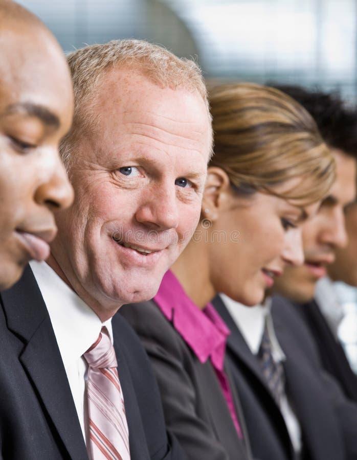 Schließen Sie oben von den Mitarbeitern, die in einer Reihe sitzen lizenzfreies stockfoto