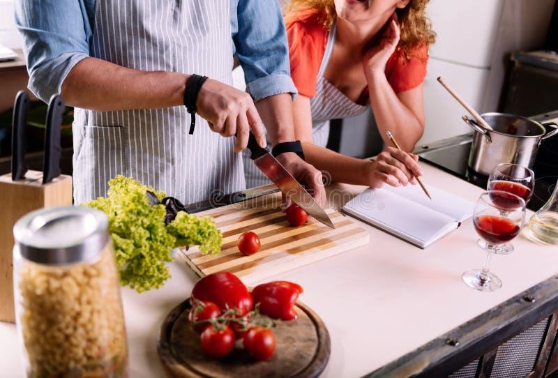Schließen Sie oben von den Paaren, die zusammen kochen lizenzfreie stockfotos