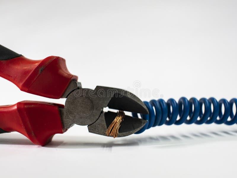 Schließen Sie oben von den roten Zangen und vom blauen verdrehten Draht auf weißem Hintergrund Zangen, die Kabel schneiden lizenzfreie stockfotos