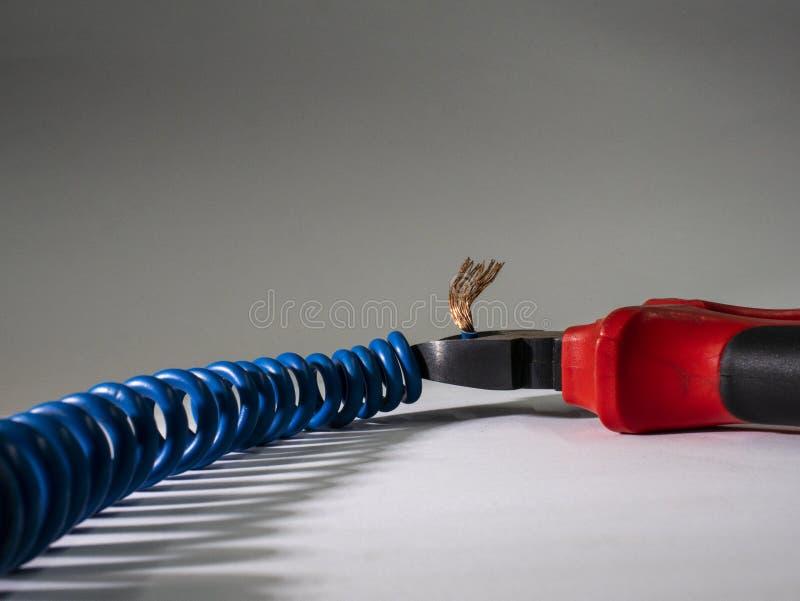 Schließen Sie oben von den roten Zangen und vom blauen verdrehten Draht auf weißem Hintergrund Zangen, die Kabel schneiden stockbilder