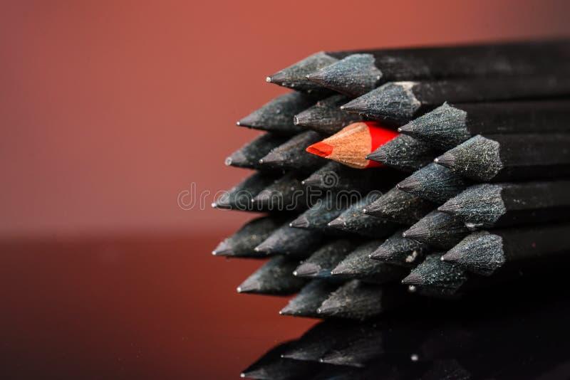 Schließen Sie oben von den schwarzen identischen Bleistiften und von einem unterschiedlichen Rot lizenzfreie stockbilder