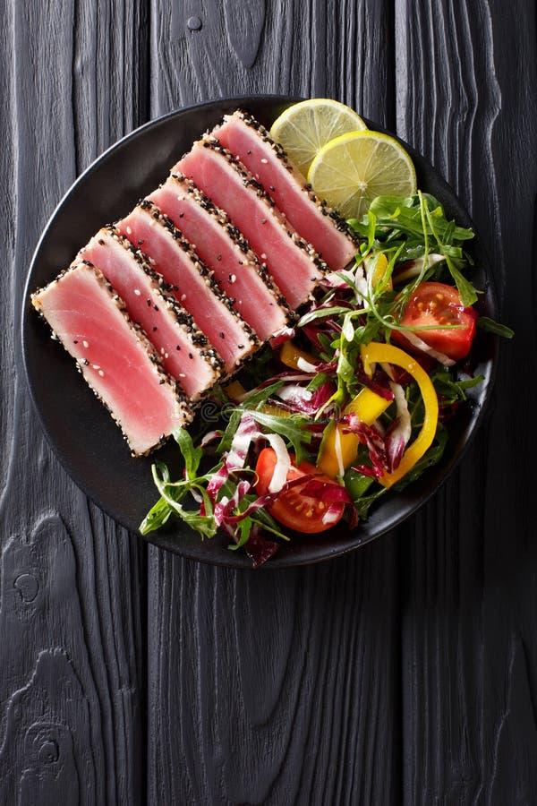 Schließen Sie oben von den seltenen verbrannten Ahi-Thunfischscheiben mit Frischgemüsesalz lizenzfreies stockfoto