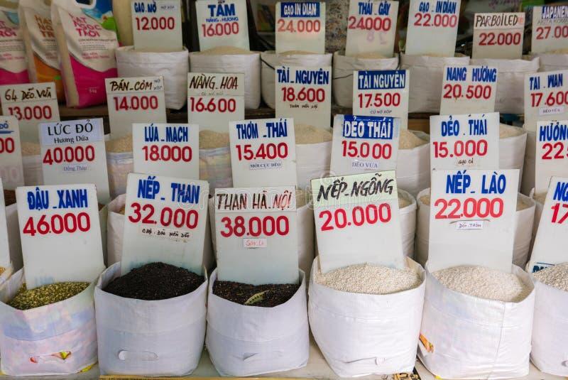 Schließen Sie oben von den Taschen des Reises in einem lokalen Markt in Vietnam mit Preis stockbilder