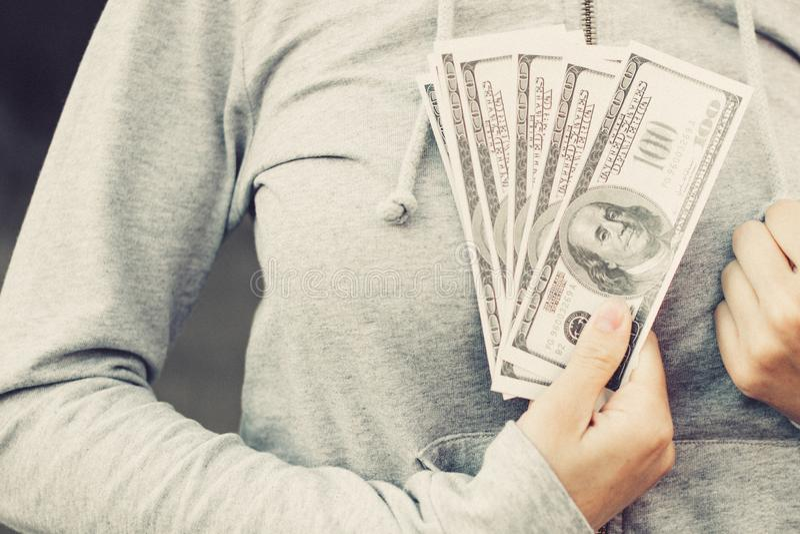 Schließen Sie oben von den US-hundertdollar-Rechnungen in der Hand Frauenpressen zu sich Banknoten stockfotografie