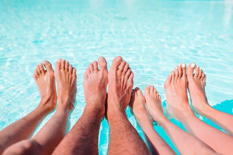 Schließen Sie oben von den vier Beinen der Leute durch Poolseite lizenzfreie stockbilder