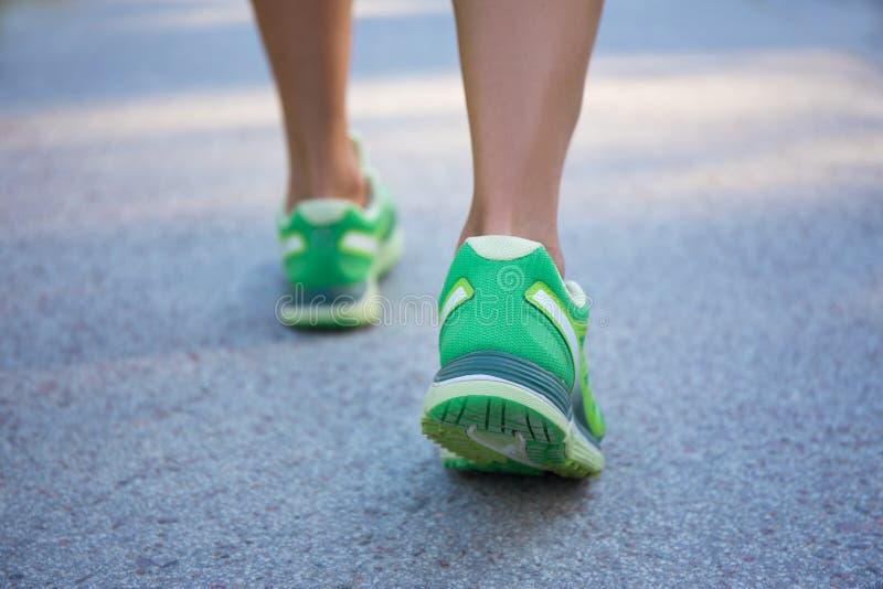 Schließen Sie oben von den weiblichen Beinen in den sportlichen Schuhen, die auf Straße laufen lizenzfreie stockfotografie
