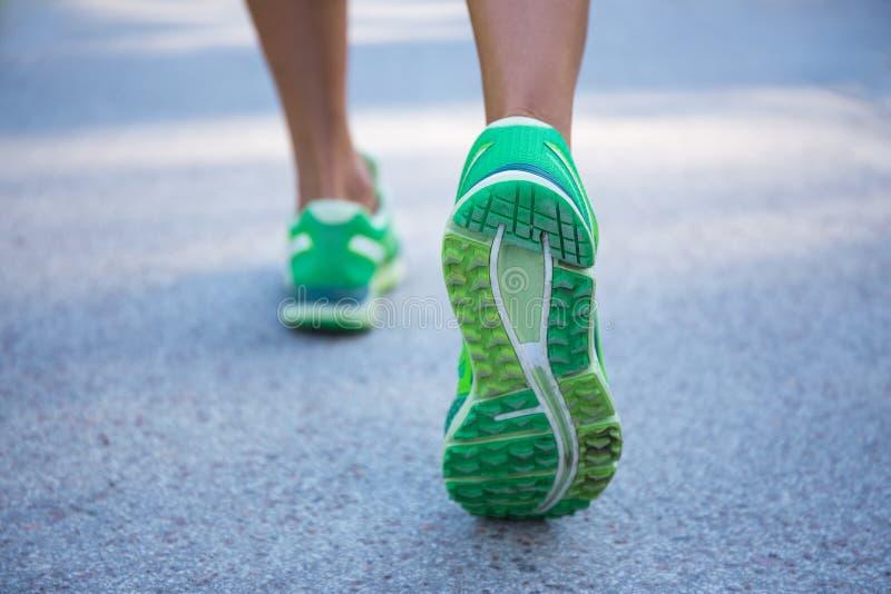 Schließen Sie oben von den weiblichen Beinen, die auf Straße laufen stockbilder