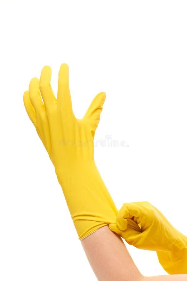 Schließen Sie oben von den weiblichen Händen, die auf gelbe schützende Gummihandschuhe gegen Weiß sich setzen stockfotografie