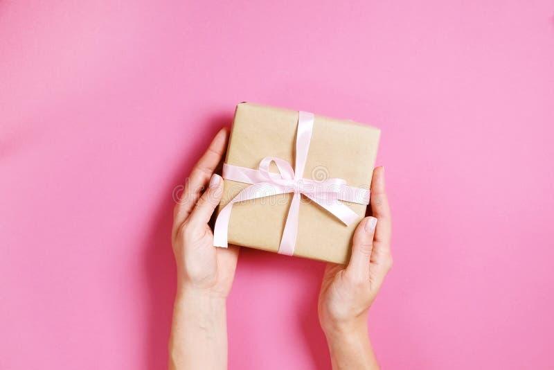 Schließen Sie oben von den weiblichen Händen, die Geburtstagsgeschenk bei der Weinlesekraftpapierverpackung halten Femenine-Zusam stockfotos