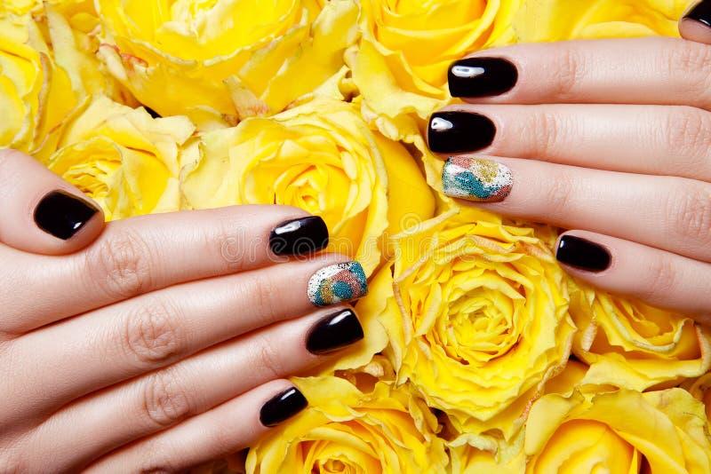 Schließen Sie oben von den weiblichen Händen, die helles Polnisches auf Nägeln tragen und gelbe Rosen halten stockfotografie