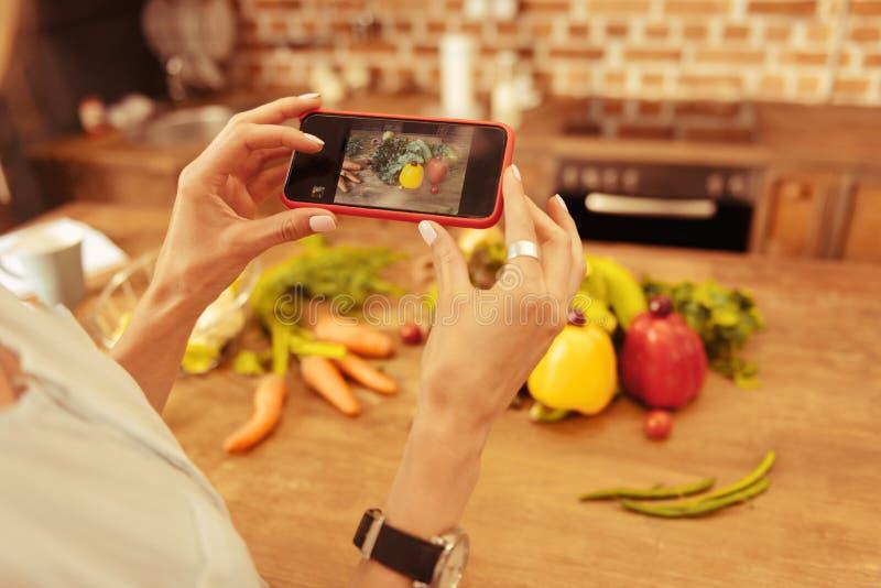 Schließen Sie oben von den weiblichen Händen, die unter Verwendung des Telefons stockbild