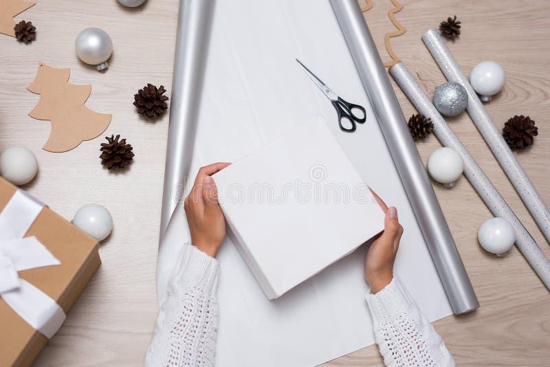 Schließen Sie oben von den weiblichen Händen, die Weihnachtsgeschenke verpacken lizenzfreies stockfoto