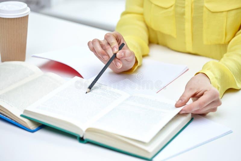 Schließen Sie oben von den weiblichen Händen mit Büchern und Kaffee stockfoto