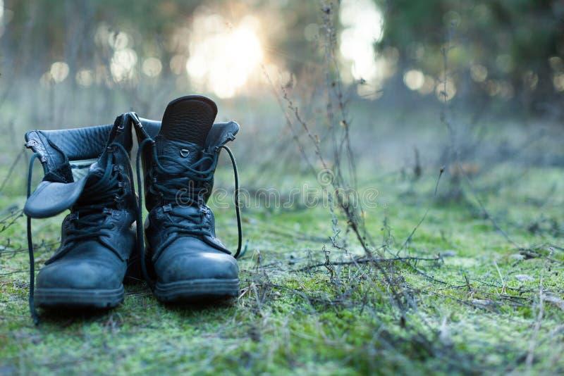 Schließen Sie oben von den Weinlesepaaren der gehenden Stiefel auf Flusssteinwiesenhintergrund lizenzfreie stockfotos