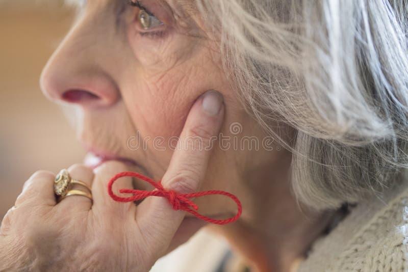 Schließen Sie oben von der älteren Frau mit der Schnur, die um Finger als Remin gebunden wird lizenzfreie stockbilder