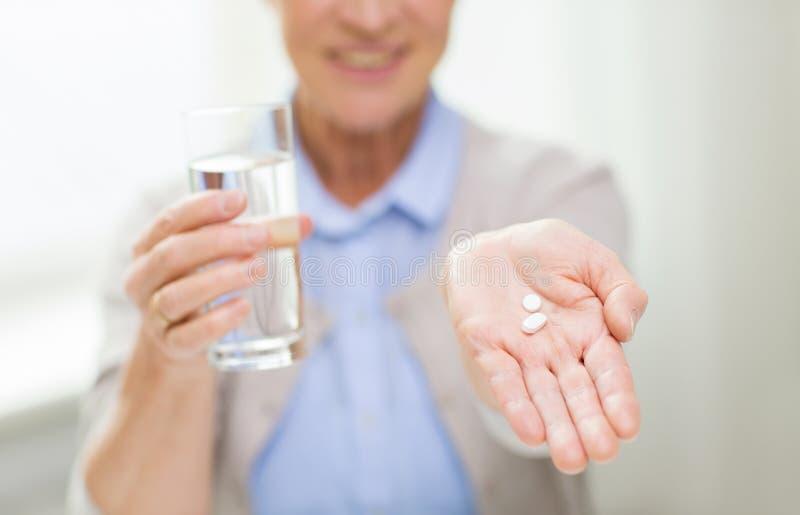 Schließen Sie oben von der älteren Frau mit Wasser und Pillen lizenzfreie stockfotografie